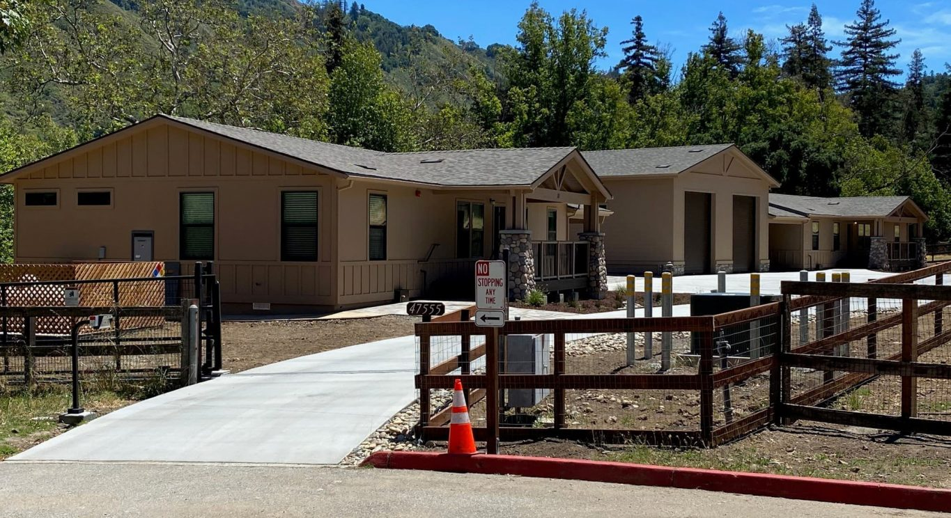 CHP government housing in Big Sur, CA. Modular construction with garage, carports, and paved driveway. Nestled in the forest.